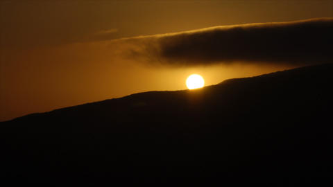 Time lapse of sun disappearing behind mountain top at sunset Stock Video Footage