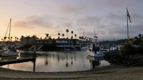 Time lapse clouds at dusk blowing over channel lined with homes and boats Footage