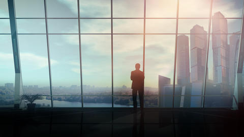 Opposite the panoramic window, a businessman stands and looks into the distance Fotografía