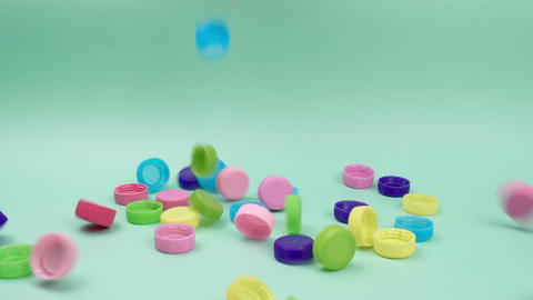 Colored plastic covers for bottles piled on top of a green background Live Action