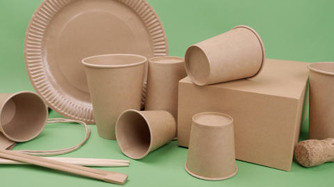 Tableware and packaging made of ecological materials on a green background Live Action