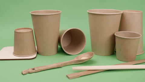 Environmental paper and wooden utensils on a green background Live Action