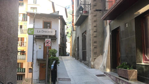 Andorra, A narrow city street with buildings on the side of a building Live Action