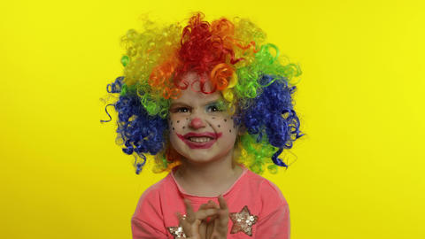 Little child girl clown in rainbow wig making silly faces, having fun, laughing Live Action