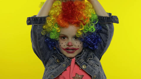 Little child girl clown in wig making silly faces, having fun with money Live Action