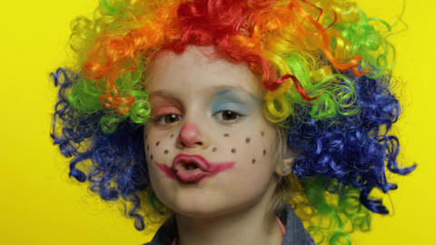 Little child girl clown in colorful wig tells something interesting. Having fun Live Action