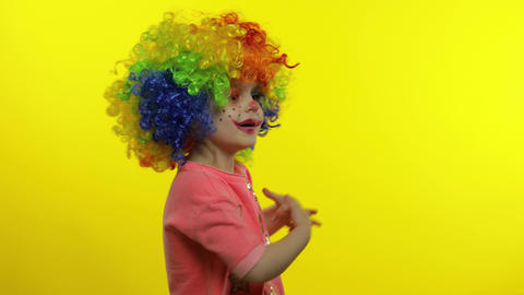 Little child girl clown in rainbow wig waving hands, having fun, smiling Live Action