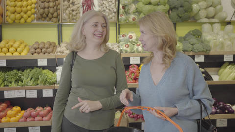 Positive Caucasian adult women talking and laughing in grocery store. Blond Live Action