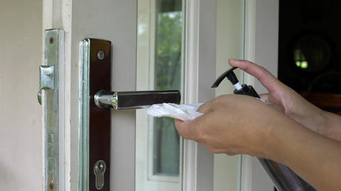 Woman cleaning and wiping door handle with sanitizer. Protection from coronavirus or covid-19 Live Action