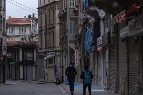 Young turkish man wearing face mask to protect from Corona virus (COVID-19) walking in the empty フォト