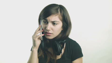 Young woman with headphones talking on her smartphone Footage