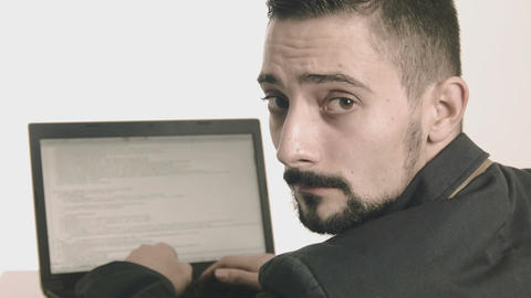 Business man computer programmer typing at his desk and looking at camera Footage