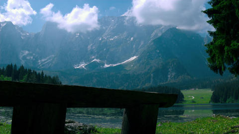 Wood bench made of logs at the lake shore with Alpine mountains in the backgroun Footage
