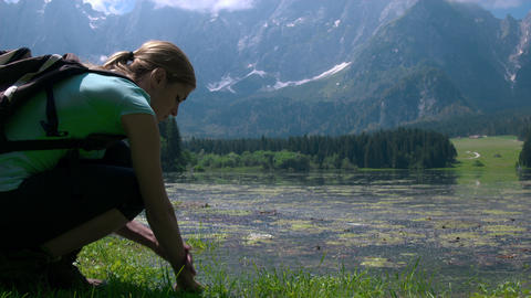 Hiking - Young woman refreshing her arms and hands with lake water Footage