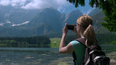 Jib shot - Young female hiker taking photos of nature with a phone Footage