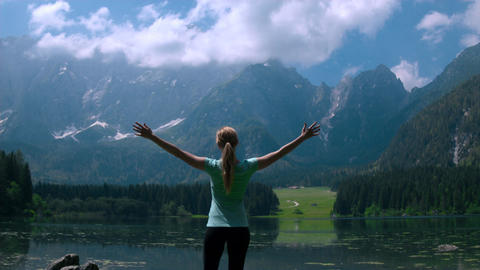 Jib shot - Fit female sport model standing near the lake with arms outstretched Footage