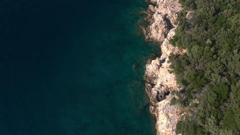 Aerial - Flying backwards above coastline of rocky shore and lush bushes Footage
