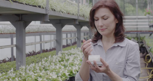 Beautiful mid-adult Caucasian woman applying organic moisturizer in greenhouse Live Action