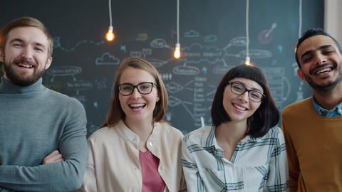 Slow motion portrait of joyful youth men and women laughing in creative office Live Action