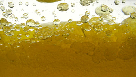 Close-up view of golden liquid in a glass. Liquid yellow wave line. Middle view Live Action