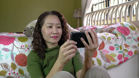 Asian Chinese businesswoman watching video on her cellphone in bedroom. Digital lifestyle Live Action