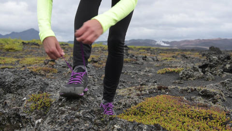 Trail run athlete woman tying laces of running shoes, getting ready for training Live Action