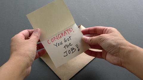 Woman open an envelope to find a card or note with the words, Congrats you got the job. Good news Live Action