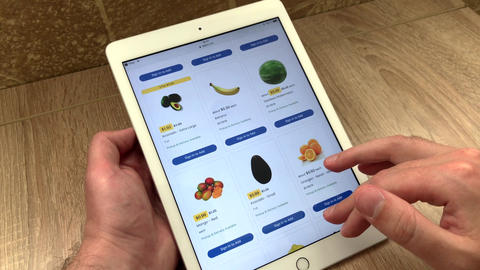 Close up selection of juicy beautiful fruits in an online store using a tablet Live Action
