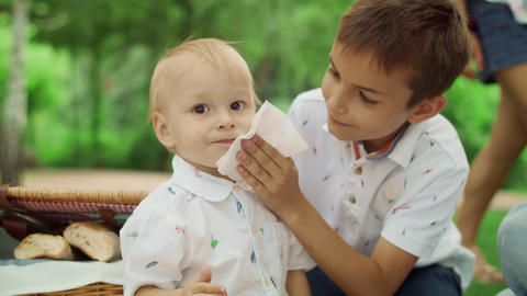 Brother taking care about small boy at picnic. Mother hand giving cherry to boy Live Action