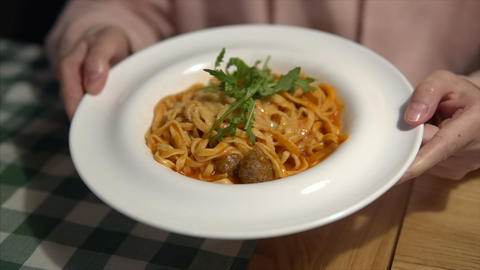 Hands of a gourmet girl hold a plate with meatballs and pasta, Italian tomato Live Action