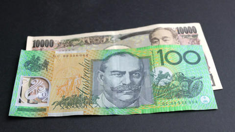 Japanese Yen and Australia Dollar side by side on white background Live Action