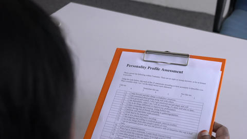 Job applicant about to fill up a personality assessment in paper form. Office table background Live Action