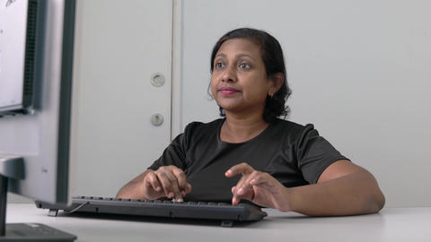 Asian Indian businesswoman typing on keyboard of her desktop computer. Work place or office setting Live Action