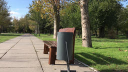 Iron trash can near a wooden bench in the park, autumn day and windy Footage