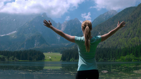 Pull back shot - Young woman with arms raised standing at... Stock Video Footage