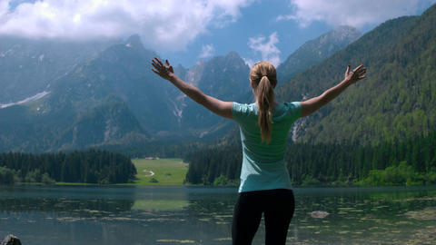 Pull back shot - Young woman with arms raised standing at lake in mountains Footage