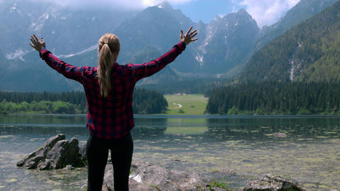 Pull back shot - Female hiker standing at the lake with arms raised Live Action