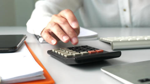 Businesswoman using the calculator on her office table. Business or finance concept Live Action
