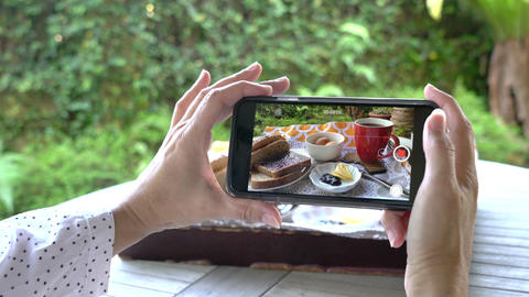 Woman taking video using her cellphone of her breakfast. Social media or digital lifestyle concept Live Action