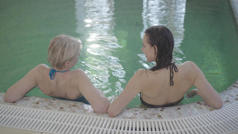 Top view of positive Caucasian women resting at poolside and talking. Back view Live影片