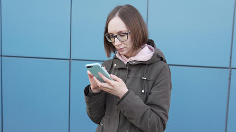 Attractive Caucasian girl hipster student in glasses using a smartphone Live Action