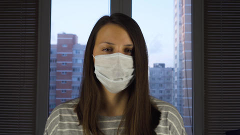 A woman in a medical protective mask stands at home against the background of Live Action