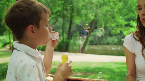 Woman having fun with son in park. Cheerful boy blowing soap bubbles outdoors Live Action