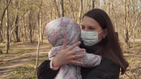 Mom with a Protective Mask with a Baby Walks in the park. Coronovirus Pandemic Live Action