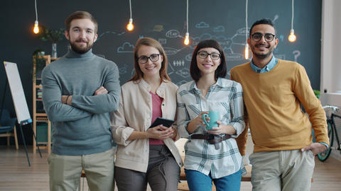 Portrait of cheerful young people coworkers standing in creative shared office Live Action