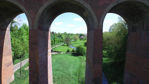 Flying through the Arches under a Viaduct on a Bright Sunny day Footage