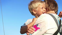 Little boy in mothers arms against blue sky, slow motion Footage
