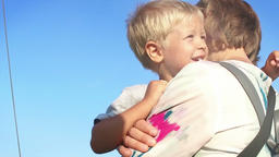 Little boy in mothers arms against blue sky, beautiful lens flare, slow motion Footage