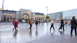 Citizens walk across square against Helsinki Central Railway Station at morning Footage