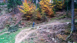 Man running into the woods, passing in front of the camera Footage
